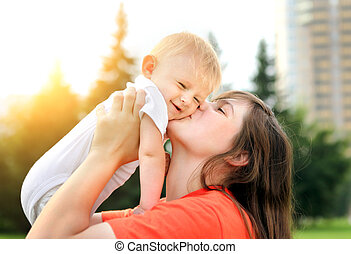 Mother and Baby outdoor - Happy Mother kiss a Little Baby...
