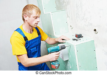 carpenter with plasterboard and screwdriver - Carpenter...