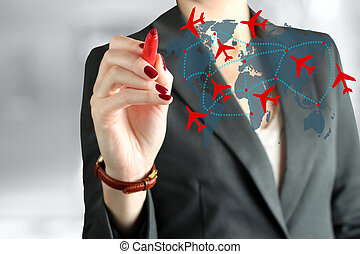Young business woman drawing an airplane routes on world...