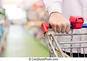 man or woman in shop with shopping trolley or cart, closeup on hand on the supermarket shelf background