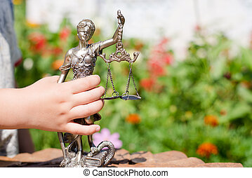Kids hand holding sculpture of themis, femida or justice...