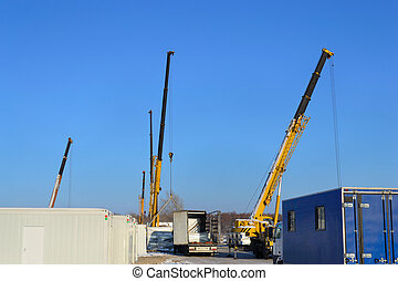 Building site with the crane trucks that unloads trucks and...