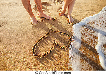 heart on the beach with couple foots close up with sea wave