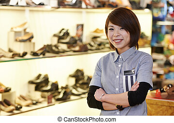chinese seller in shoe shop - chinese young smiling female...