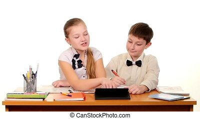 School children sitting by the table and doing homework, on white background, slow motion