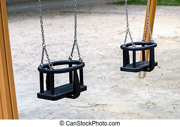 Empty playground swings - Empty playground swing close up...