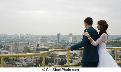 rear view shot of bride and groom looking at urban city from...