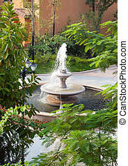 Fountain in Garden - Fountain and trees in Garden
