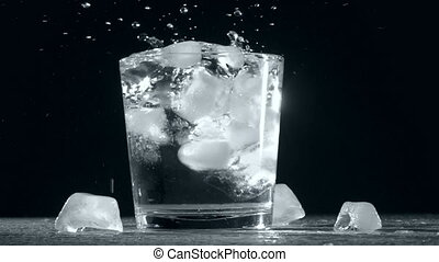 Splash of ice cube in glass water isolated on black background. Slow motion.