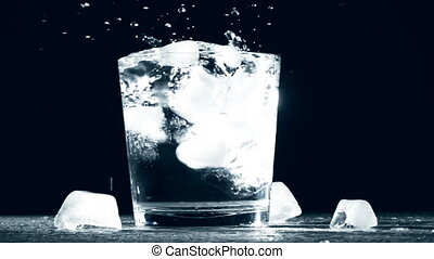 Splash of ice cube in glass water isolated on black...