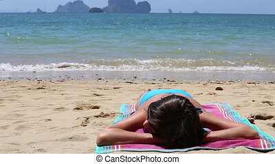 young girl lies on beach at sea against islands