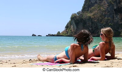 young girls tan sitting on bath towel - young brunette and...