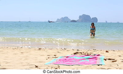 young girl comes out of sea lies down on beach towel - young...