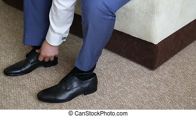 Man is tying his black shoes Close-up