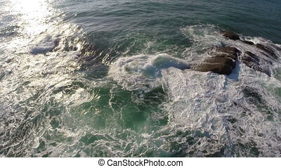 flying over sea waves and stones at sunrise
