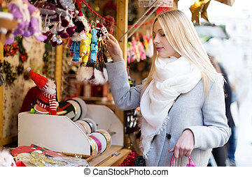 girl shopping at Christmas market - cheerful beautiful girl...