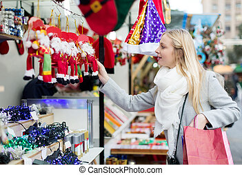 girl shopping at Christmas market - young blonde woman...