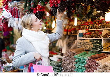girl chooses to holiday decor - beautiful blonde girl...
