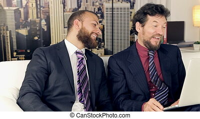 business men laughing in office - Two business men having...