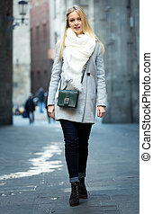 Blond woman walking on a street - Beautiful young woman...