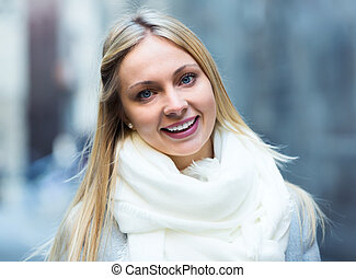 Smiling girl on a city street - Smiling blonde girl in coat...