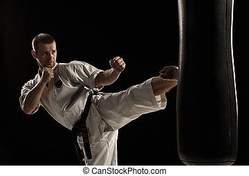 Karate round kick in a punching bag - Man in white kimono...