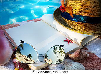 art Straw hat , book and Sunglasses on the beach