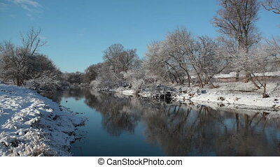 Winter landscape with the river and trees ashore in a sunny day