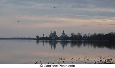 Seagulls fly over Nero's lake against Spaso-Yakovlevsky...