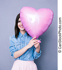 Smiling woman covering her eye with heart shaped balloon...