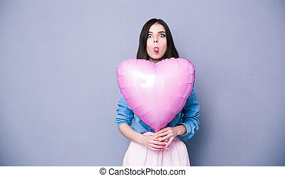 Woman holding heart shaped balloon and showing her tongue...