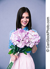 Happy young woman holding flowers over gray background