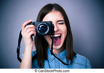 Cheerful young woman making photo on camera over gray...