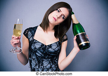 Pensive woman holding two glass and bottle of champagne over...