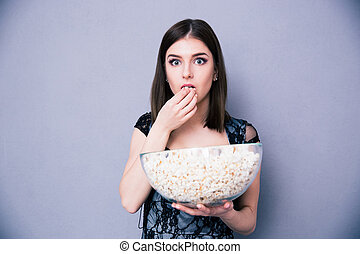 Young amazed woman eating popcorn over gray background....