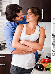 husband hold is wife in the kitchen and about to kiss