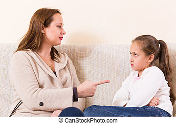 Mother scolding little daughter - Mother sitting on sofa and...