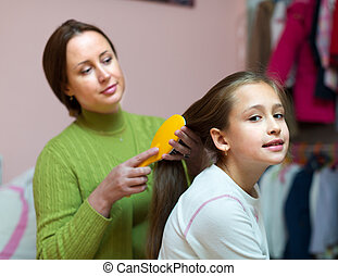 Mom taking care of daughter hair - Mom taking care of little...