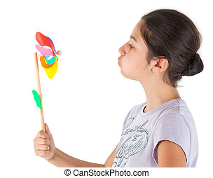 Teenager blowing a colored pinwheel