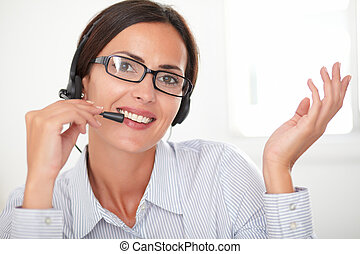 Pretty female employee talking on headphones - Pretty female...