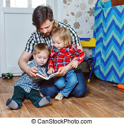 Father reading a book to children