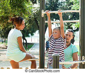 Training on chin-up bar - Happy couple with teenager child...