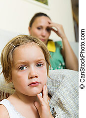 Sad child against unhappy woman having quarrel