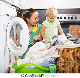Woman with child near washing machine - Home laundry....