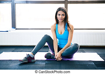 Thoughtful fit woman sitting on yoga mat and looking at...