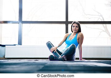 Pensive woman sitting on yoga mat at gym and looking up