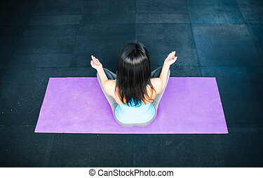 Back view portrait of a woman meditating on yoha mat at gym