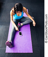 Woman sitting on the yoga mat and looking on smartphone -...