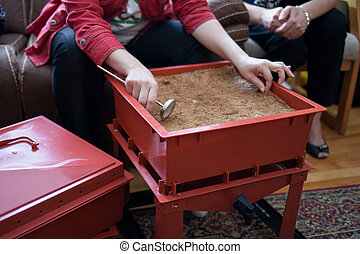 Composting - Woman showing her composting box to other...