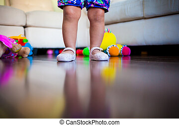 Baby Legs - Legs of a baby in the living room with toys on...